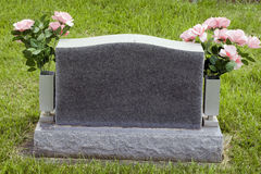 Gravestone. Blank granite gravestone with pink flowers in the vases on the sides Royalty Free Stock Photography