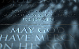 Gravestone Of Convicted Murderer. A 3D render of closeup of a carved and etched tombstone of a convicted murderer Stock Photo