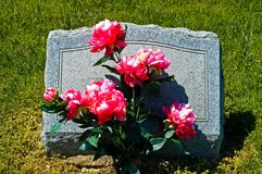 Gravestone in Country Cemetery. Small gravestone with flowers in a community cemetery stock images