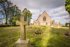 Gravestone Cross at Heavenfield. A delightful hilltop church in Northumberland, believed to be the location where King Oswald raised a large wooden cross before Stock Photo
