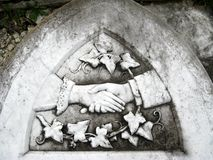 Gravestone: farewell handshake. Victorian marble gravestone with clasped hands and ivy tendrils Royalty Free Stock Photo
