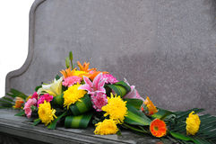 Gravestone and flower. A bunch of flowers front of gravestone royalty free stock photography
