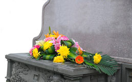Gravestone and flower. A bunch of flowers front of gravestone Royalty Free Stock Images