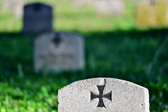 Gravestone of a german soldier. With the iron cross symbol in a heroes graveyard Royalty Free Stock Photos