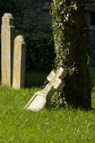 Gravestone leaning on an ivy clad tree Stock Image