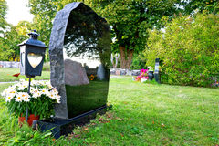 Gravestone with reflection. Graveyard with flowers, lantern and gravestone with reflection stock photo