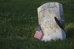 Gravestone in spring. Gravestone with American flag in a field of grass and flowers. Space on headstone to insert any text or name stock image