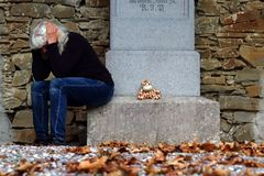 A gravestone with toys and a sad woman royalty free stock image