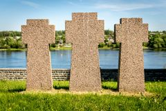 Three Small cross gravestones in a row. Gravestones in a German second world war cemetery. Narva in Estonia. trees in war memorial area. green field. leaves and royalty free stock photos