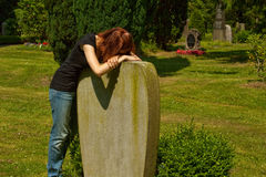 Graveyard. Young woman leaning on a tombstone. She mourns her husband Royalty Free Stock Photos