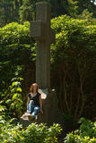 Graveyard. A young woman sitting on a tomb. She thinks of her late husband royalty free stock images