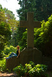 Graveyard. A young woman sitting on a tomb. She thinks of her late husband Royalty Free Stock Photography