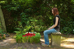 Graveyard. Young woman sitting on a bench before a fresh grave royalty free stock image