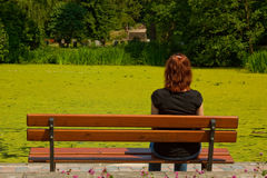 Graveyard. Young woman sitting at a pond in a cemetery. It mourns a relative stock photo