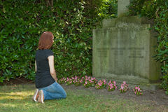 Graveyard. Young woman kneeling before a grave Royalty Free Stock Photos