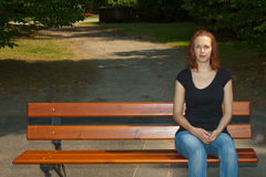 Graveyard. Young woman sitting on a bench and mourning the death of one belonging Stock Image