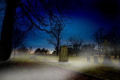 Graveyard. A spooky graveyard at sundown with mist royalty free stock images