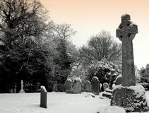 Graveyard. Old graves in the snow in an old graveyard in england. Monotone image with slight sky tint Royalty Free Stock Photo
