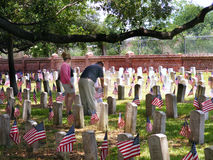 Graveyard with American Flags and Visitors. National Cemetery in Chalmette, Louisiana Civil War Era Headstones with American Flags Royalty Free Stock Photo