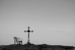 Graveyard cross in silhouette. Graveyard cross and bench in silhouette. copy space Royalty Free Stock Images