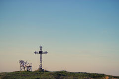 Graveyard cross in silhouette. Graveyard cross and bench in silhouette. copy space Stock Image