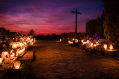 Graveyard with moved silhouettes ghosts and a cross late in the evening. royalty free stock photos