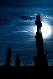 Graveyard at night three tombstones moonlight. Cemetery at sunset with the silhouette of three tombstones silver moon Royalty Free Stock Image