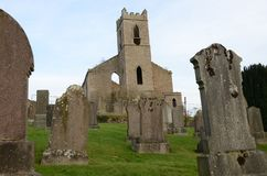 Graveyard and Ruined Church Building in Bankfoot, Perthshire. A view across an old graveyard toward a ruined church building in the village of Bankfoot in Stock Photos