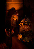 Graveyard shift. Old bearded man (puppet) sitting at a graveyard at a lit up tomb; a Halloween set-up stock photo