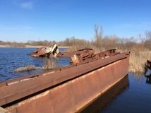 Graveyard of ships on the river.  Many rusty barges and boats in water Stock Photos