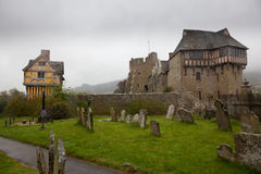 Graveyard by Stokesay castle in Shropshire. Stokesay Castle in England on damp raining day from cemetery Stock Photo