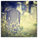 Graveyard. Tombstone and graves in an ancient church graveyard with Instagram style filter effect Stock Images