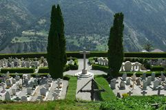 Graveyard with a View. Village graveyard in Swiss Alps with a view. Two large cyrpus trees flank a cross in an immaculately maintained cemetry Royalty Free Stock Images