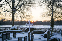 Graveyard in winter with sunset and snow Royalty Free Stock Image