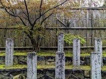 Gravez le pilier japonais de pierre de granit de lettrage sur l'arbre a de Sakura Photographie stock libre de droits