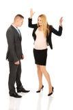 Gravid affärskvinna som argumenterar med hennes partner Arkivfoto