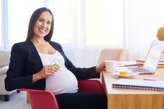 Gravid affärskvinna som dricker te och äter makron arkivbilder