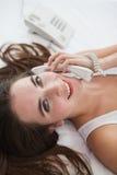 Gravid brunett på telefonen i säng Royaltyfri Bild