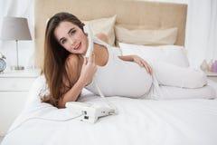 Gravid brunett på telefonen i säng Royaltyfri Fotografi