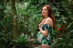 Gravid caucasian rödhårig mankvinna för barn i baddräkt på tropiskt G Arkivbilder