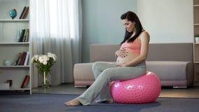 Gravid dam för barn som lyssnar till hennes slå för babys som sitter på konditionboll arkivbild