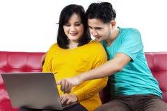Gravid dam och make som använder bärbara datorn Fotografering för Bildbyråer