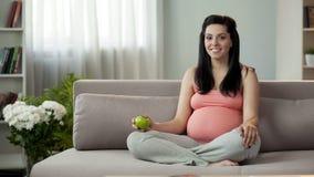 Gravid dam som äter nya frukter som bor den sunda livsstilen som tar omsorg av barnet fotografering för bildbyråer