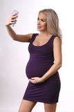 Gravid flicka i en klänning som tar selfie close upp Vit bakgrund Royaltyfri Foto