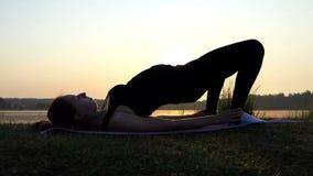 Gravid flicka Iies på Mat And Raises Her Belly på en sjöbank på solnedgången stock video