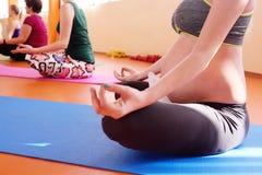 Gravid flicka som är förlovad i kondition samman med en grupp av yoga i en sportklubba fotografering för bildbyråer