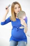 Gravid flicka som borstar hennes hår Arkivfoto