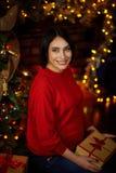 Gravid flickasammanträde med gåvor på en julgran arkivbild