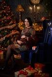 Gravid flickasammanträde med gåvor på en julgran arkivfoton
