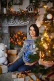Gravid flickasammanträde med gåvor på en julgran royaltyfri bild